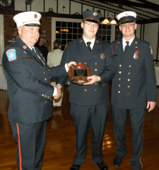 3 firefighters holding a plaque