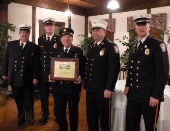 4 men in navy blue uniforms and one man holding a plaque